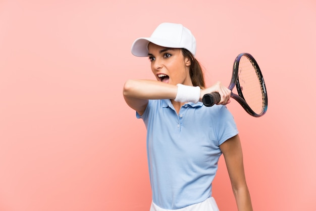 De jonge vrouw van de tennisspeler over geïsoleerde roze muur