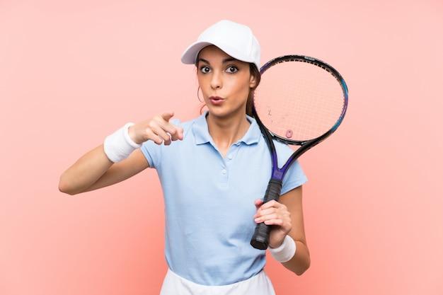 De jonge vrouw van de tennisspeler over geïsoleerde roze verrast muur en het richten van voorzijde