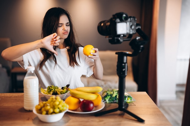 De jonge vrouw van de voedselblogger houdt niet van vers fruit en salade in de keukenstudio, filmt tutorial op camera voor videokanaal. vrouwelijke influencer toont voorkeur in eten, praat over eten.