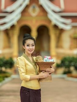De jonge vrouw van glimlach van de aziatische vrouw van de zijdekleding in zijdekleding in tempel
