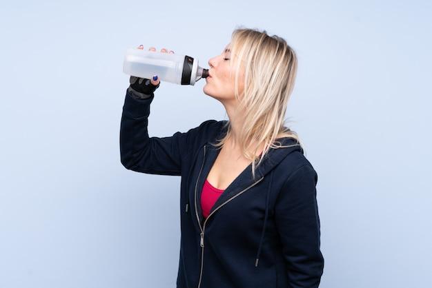 De jonge vrouw van het sportblonde over geïsoleerde blauwe muur met de fles van het sportenwater