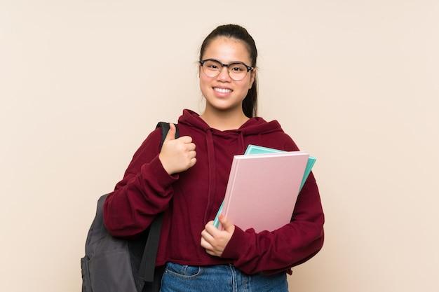 De jonge vrouw van het studenten aziatische meisje over het geïsoleerde muur geven duimen op gebaar