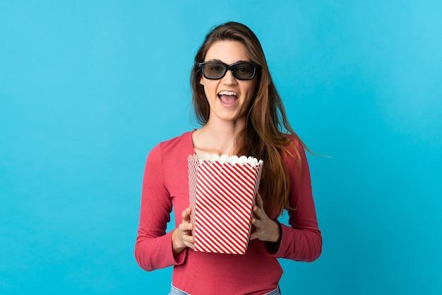 De jonge vrouw van ierland die met 3d glazen wordt geïsoleerd en een grote emmer popcorns houdt