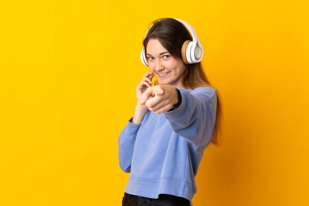 De jonge vrouw van ierland die op gele muur wordt geïsoleerd, muziek luistert en naar voren wijst