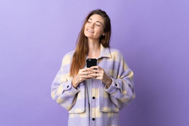 De jonge vrouw van ierland die op purpere muur wordt geïsoleerd die mobiele telefoon met behulp van en omhoog kijkt