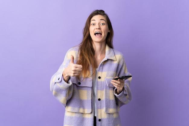 De jonge vrouw van ierland die op purpere muur wordt geïsoleerd die mobiele telefoon met behulp van terwijl het doen van duimen omhoog