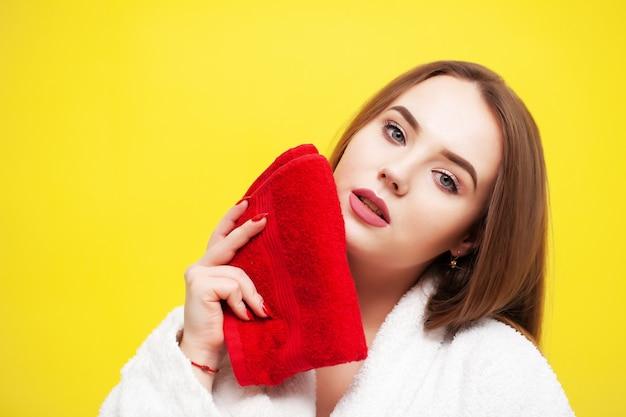 De jonge vrouw veegt gezicht met zachte handdoek af na kuuroordbehandelingen.