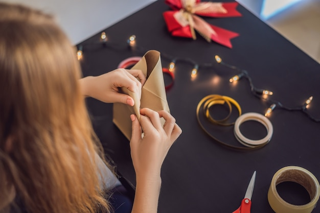 De jonge vrouw verpakt cadeautjes. cadeau verpakt in knutselpapier met een rood en goud lint voor