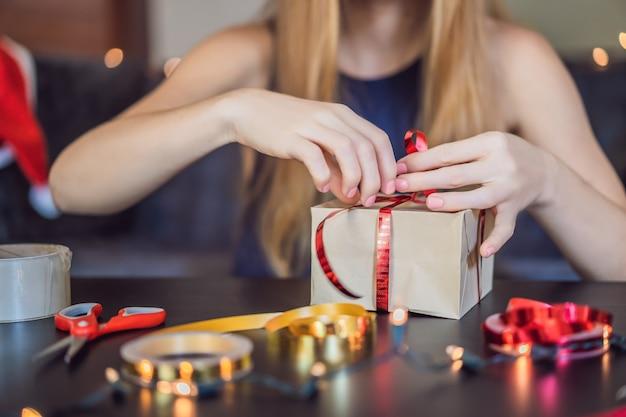 De jonge vrouw verpakt cadeautjes. cadeau verpakt in knutselpapier met een rood en gouden lint voor kerst