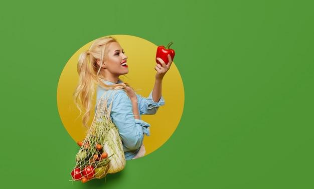 De jonge vrouw verzamelde verse groenten in een koordzak op een groene achtergrond. gluurt uit een rond gat in de muur.