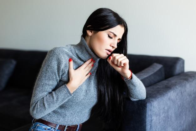 De jonge vrouw voelt zich ziek thuis op bank wordt gevoeld