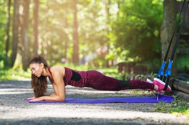 De jonge vrouw voert een plankoefening uit met geschiktheidsriemen in de frisse lucht