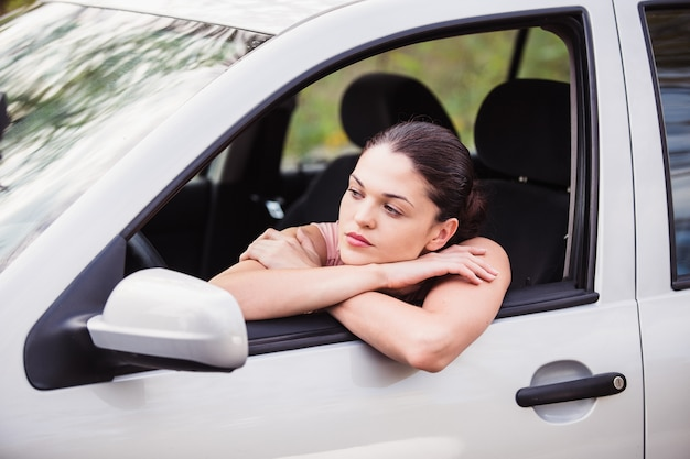 De jonge vrouw wacht op hulp dichtbij haar auto, die op de wegkant opsplitst