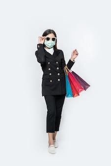 De jonge vrouw was gekleed in het donker, een masker en een bril en tassen om boodschappen te doen