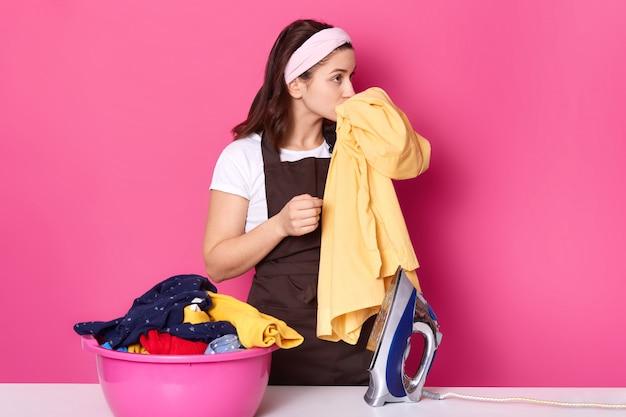 De jonge vrouw werkt als meid, draagt een t-shirt, een bruine schort en een haarband, staat in de buurt van een roze bak met schoon linnen dat op een roos in de fotostudio staat, ruikt frisse kleding en heeft een aangename geur.