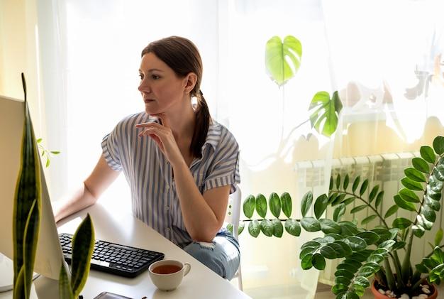De jonge vrouw werkt thuis bij een bureaucomputer in quarantaine
