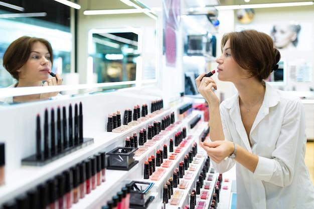 De jonge vrouw zet op rode lippenstift bij schoonheidsmiddelenwinkel