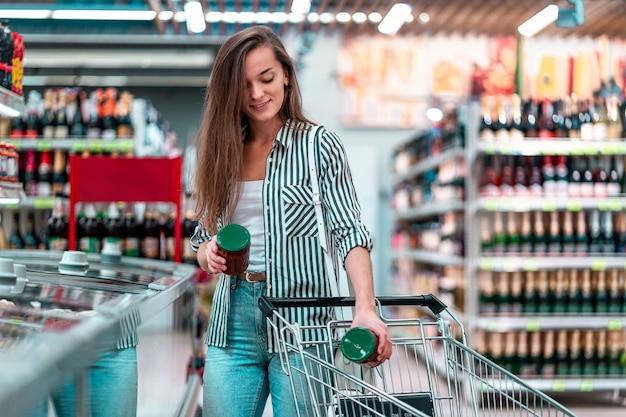 De jonge vrouw zet voedsel in een boodschappenwagentje in een supermarkt. klant kopen van producten in de supermarkt