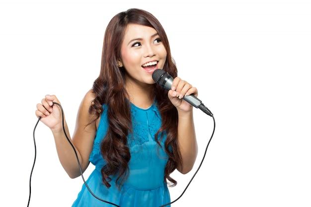 De jonge vrouw zingt houdend een mic, geïsoleerd