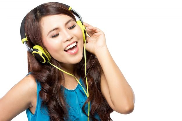 De jonge vrouw zingt terwijl het luisteren aan muziek met hoofdtelefoons