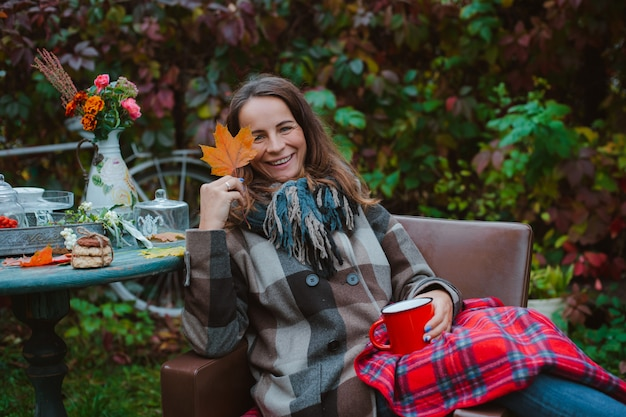 De jonge vrouw zit buiten stoel met koffiemok