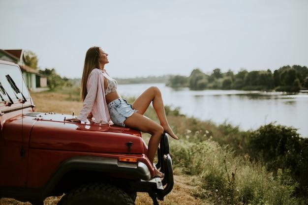 De jonge vrouw zit op een rode autokap en geniet van in de zomerzon