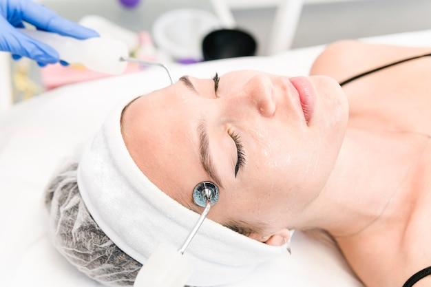 De jonge vrouwelijke cliënt van kosmetische salon die microstroomprocedure op haar gezicht heeft