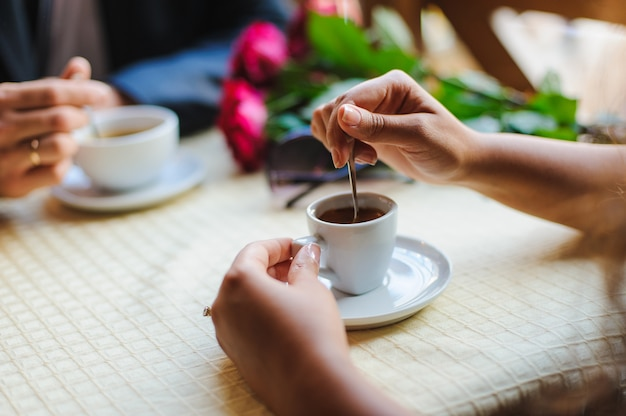 De jonge vrouwelijke hand beweegt kop van koffie bij koffie