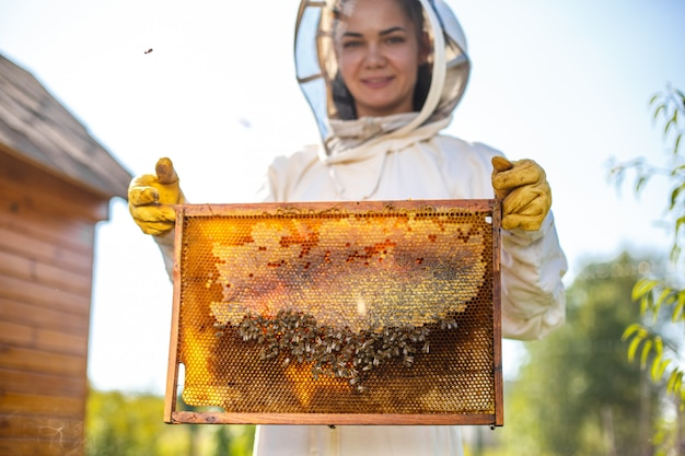 De jonge vrouwelijke imker houdt houten frame met honingraat
