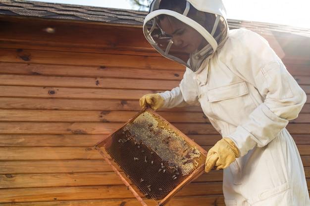 De jonge vrouwelijke imker houdt houten frame met honingraat.