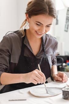 De jonge vrouwelijke keramist die door werkt dient aardewerkstudio in.