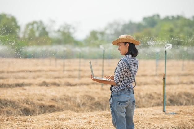 De jonge vrouwelijke landbouwer van azië in hoed die zich in gebied bevindt en op toetsenbord van laptop computer typt. vrouw met laptop toezicht op het werk op landbouwgrond, concept ecologie, vervoer, schone lucht, voedsel, bioproduct