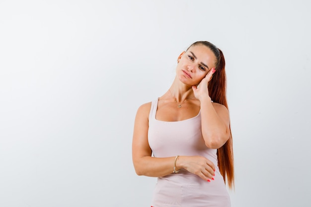 De jonge vrouwelijke leunende wang dient wit mouwloos onderhemd in en kijkt moe. vooraanzicht.