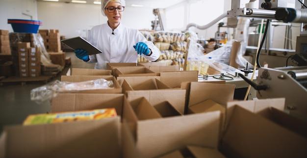 De jonge vrouwelijke werknemer in steriele kleren gebruikt tablet om het juiste aantal pakketten te controleren.
