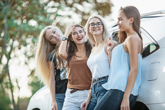 De jonge vrouwen die en zich dichtbij de auto bevinden glimlachen openlucht. het concept van levensstijl, reizen, avontuur en vrouwelijke vriendschap
