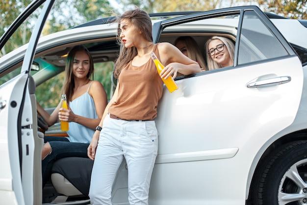 De jonge vrouwen in de auto en het drinken van sap en glimlachend buiten. het concept van levensstijl, reizen, avontuur en vrouwelijke vriendschap