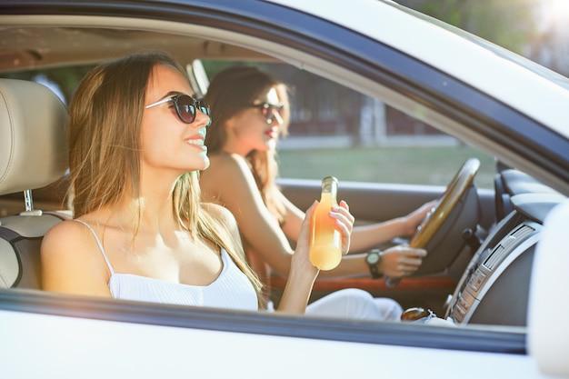 De jonge vrouwen in de auto glimlachen