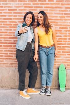De jonge vrouwen koppelen het maken van een selfie in een bakstenen muur.