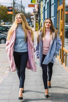 De jonge vrouwen van de blonde met dient zak in lopend op straat Gratis Foto