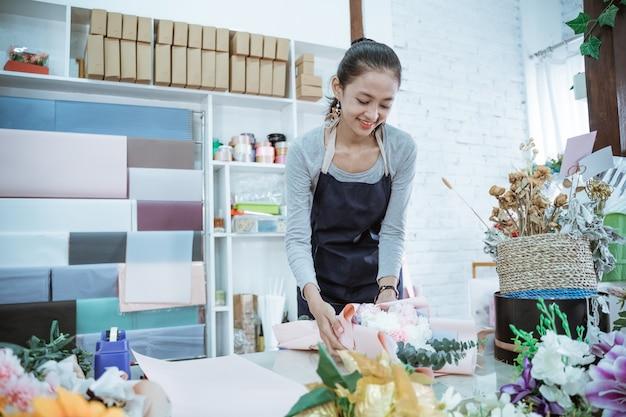 De jonge vrouwenbloemist die in bloemenwinkel werkt, maakt ordeflanelbloem in een lijstwerkruimte