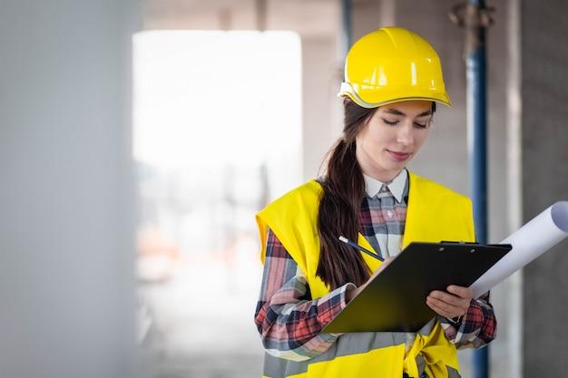 De jonge vrouwenbouwer vult bouwdocumenten in