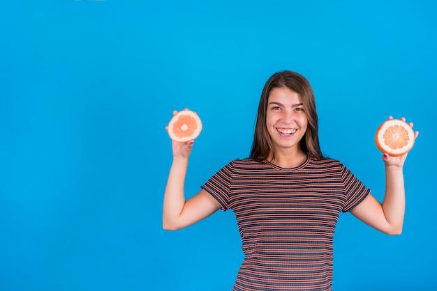 De jonge vrouwenholding de helften sinaasappelen op blauwe achtergrond