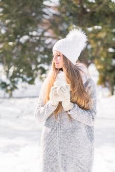 De jonge vrouwenholding haalt koffiekop in handen weg genietend in de winter