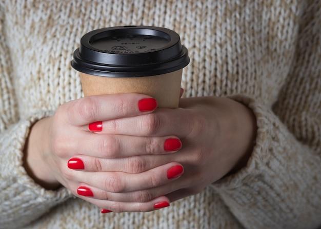 De jonge vrouwenholding in handenspatie haalt de kop van de kraftpapierkoffie, lichtbeige sweater weg.