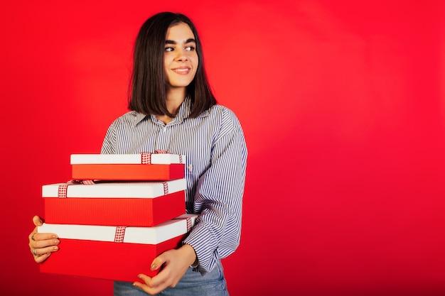 De jonge vrouwenholding stelt dozen voor die over rode muur worden geïsoleerd