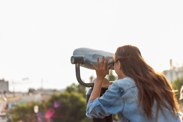 De jonge vrouwentoerist in een denimjasje en glazen kijkt in de stadsverrekijkers in de stad. reizen concept