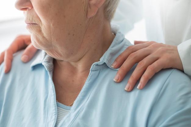 De jonge vrouwenverzorger steunt een bejaardepatiënt.