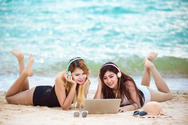 De jonge vrouwenvrienden luisteren muziek op het strand, de zomerconcept.
