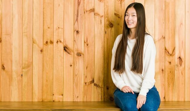 De jonge vrouwenzitting op een houten plaats kijkt opzij glimlachend, vrolijk en aangenaam