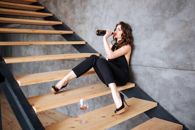 De jonge vrouwenzitting op stappen en drinkt wijn van fles